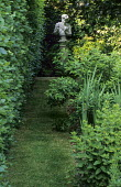 View along beech hedge towards Pan statue on plinth, grass path